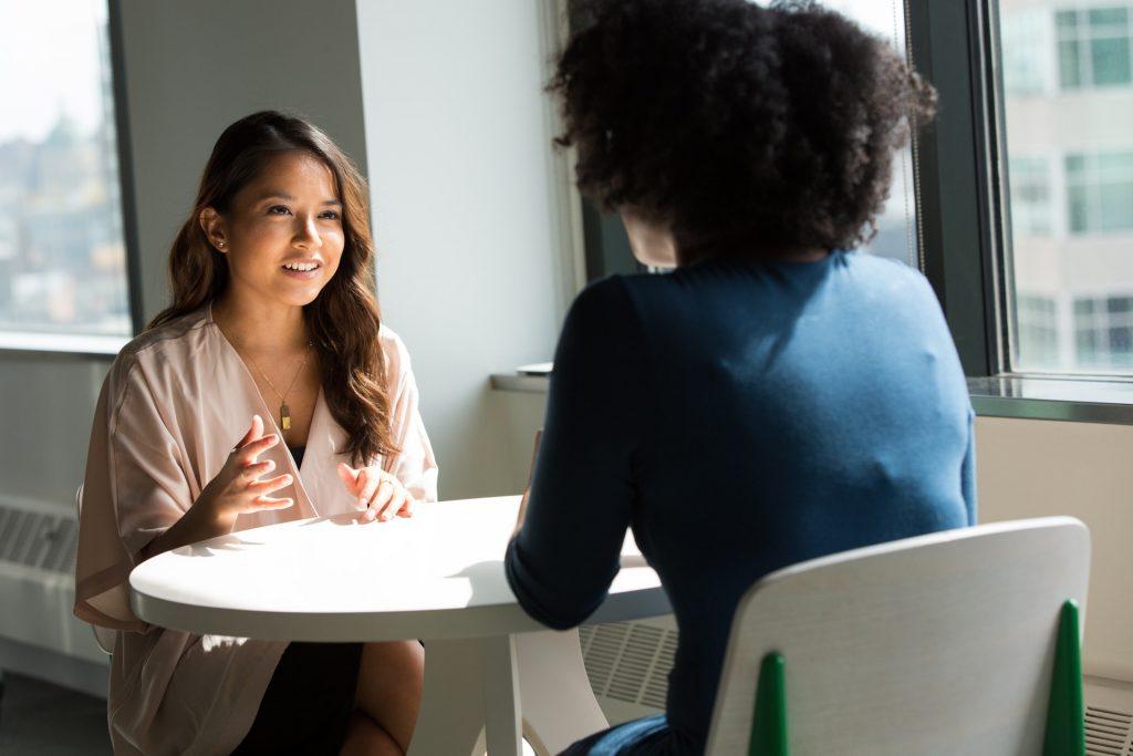 Dwie kobiety siedzące przy stole i rozmawiające.